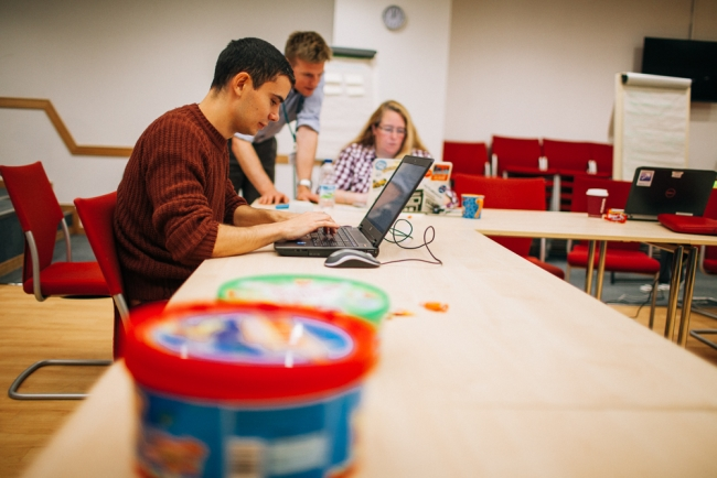 People working on laptops with jar of sweets in foreground