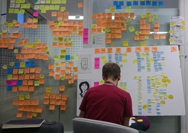 researcher facing wall of Post-it notes