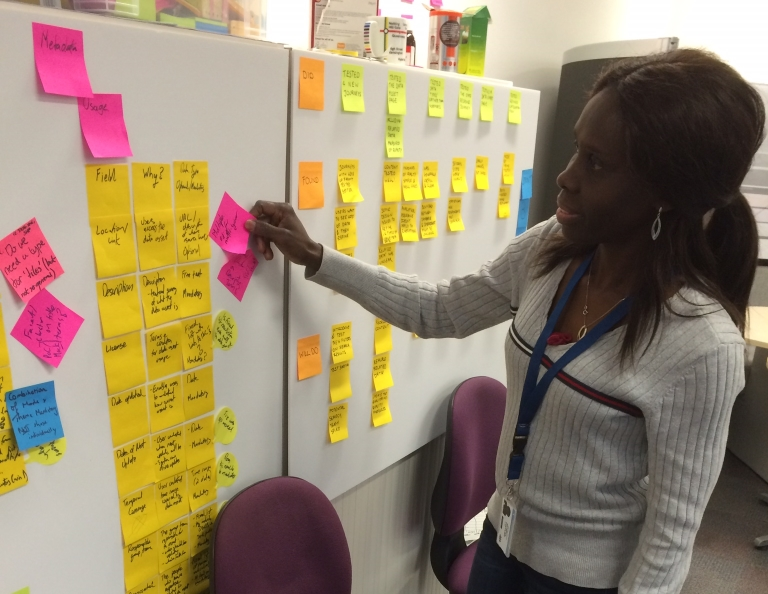 woman putting Post-it note on a kanban board
