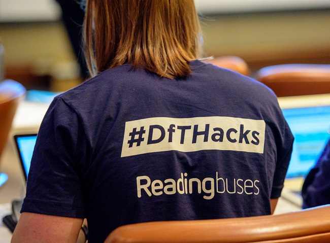 back of a person wearing a DfT Hacks branded t-shirt