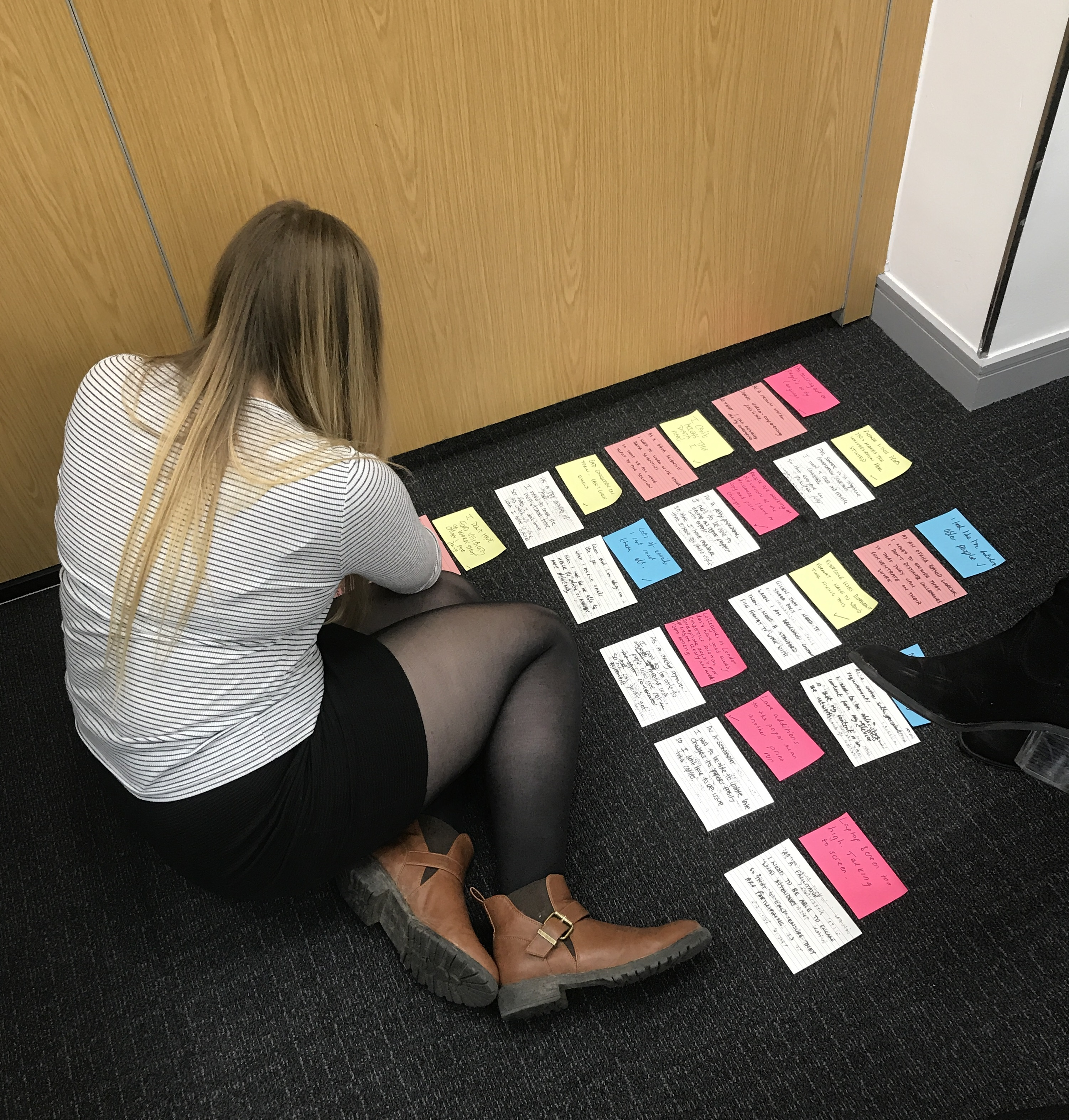 Gemma doing a card sort on a corner of the office floor