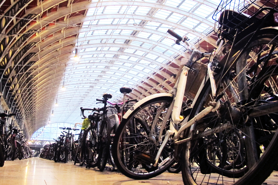 closeup view of many bikes parked under a large glass roof