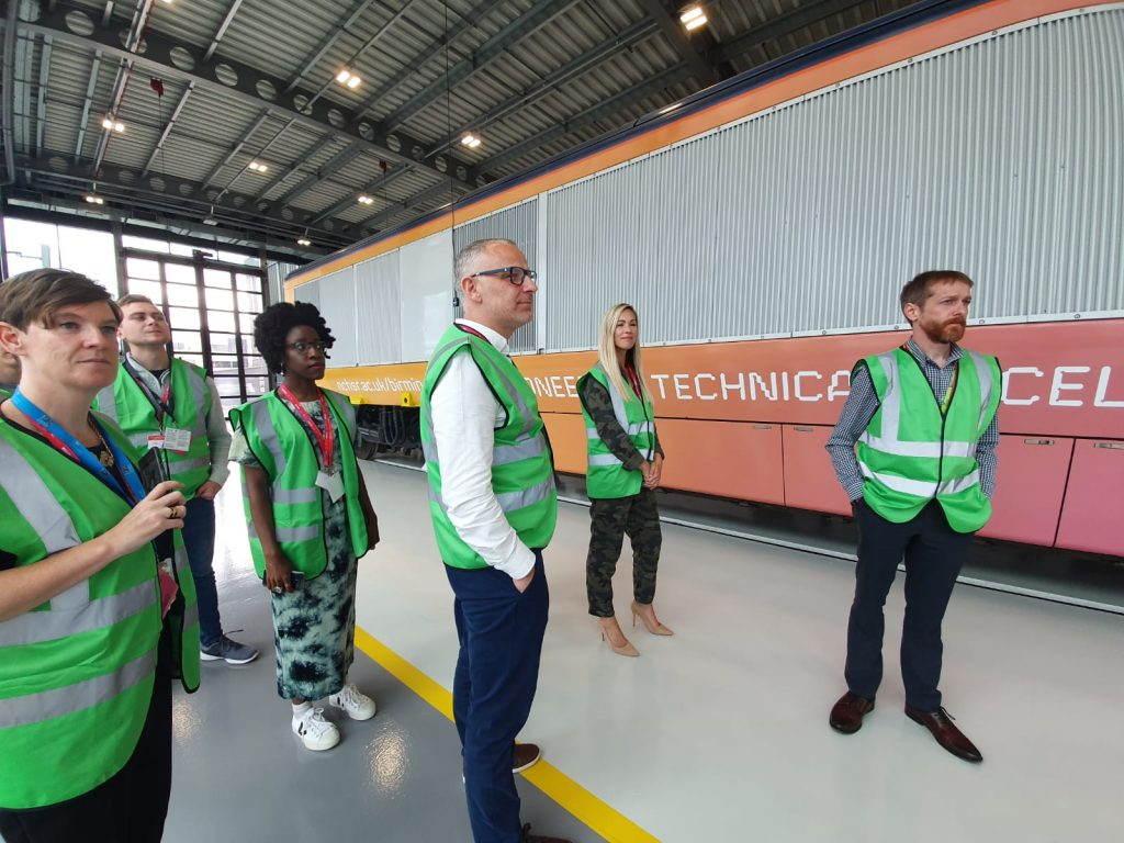 An image of 6 civil servants in high visibility vests learning about high speed rail in front of a train