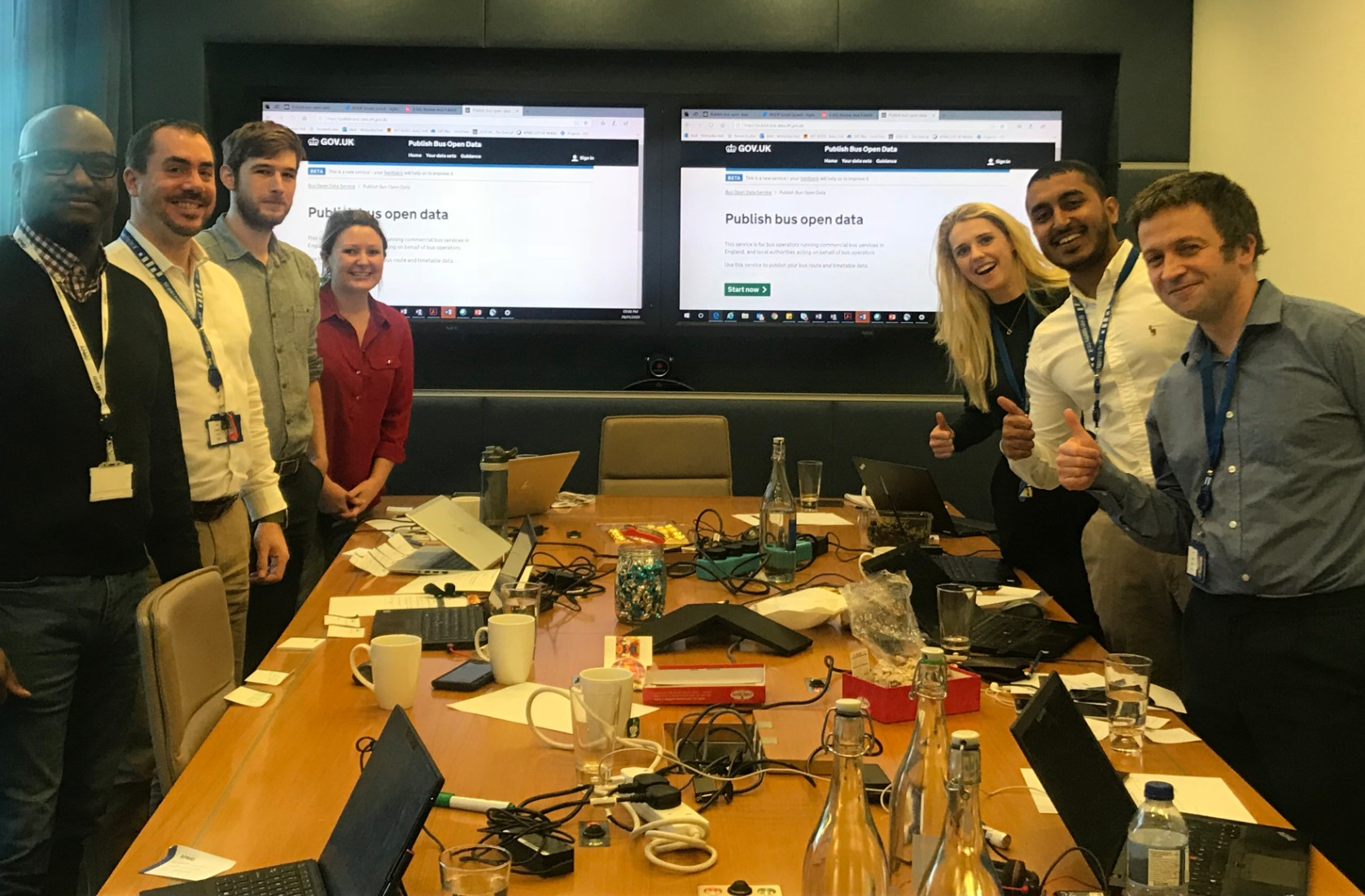 the Buses Open Data team around a meeting table, smiling for the camera
