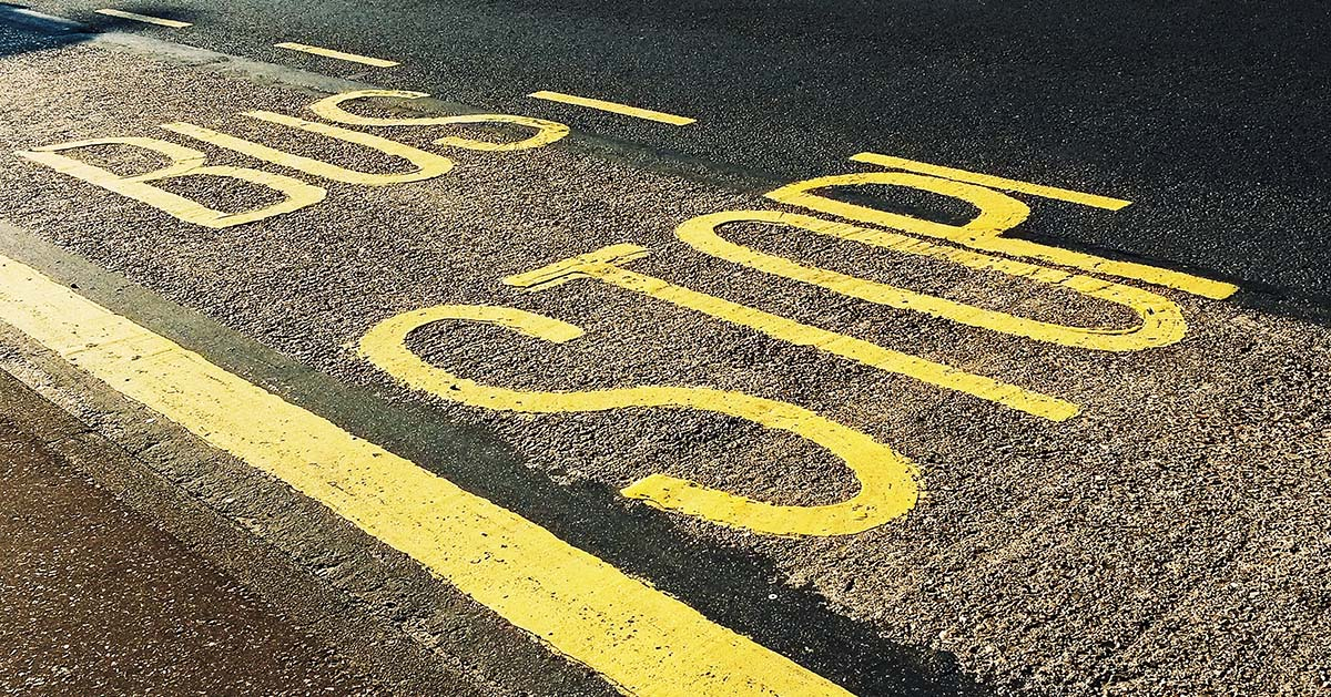 Bus stop painted lettering on tarmac road